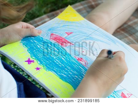 A Little Girl Paints With Felt-tip Pens In The Album. A Close-up Photo.