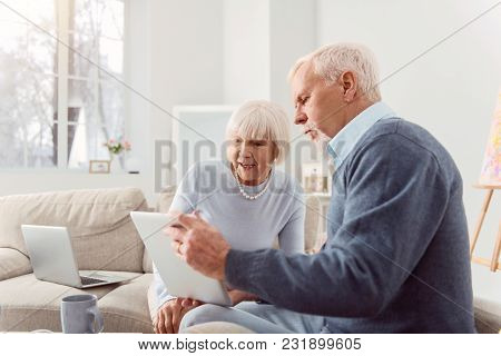 Share Your Opinion. Pleasant Bearded Elderly Man Showing His Wife A Tablet With A Social Media Post