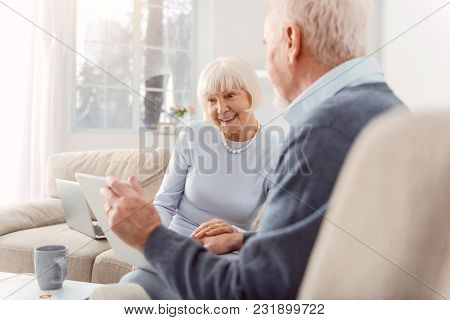 Loving Grandparents. Pleasant Elderly Man Showing His Wife The Tablet With The Photos Of Their Grand