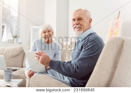 Mood-boosting Message. Joyful Elderly Man And His Beloved Wife Sitting In The Living Room And Watchi