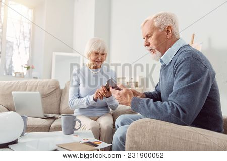 Addicted To Gadgets. Pleasant Senior Couple Sitting In The Living Room And Being Glued To Their Gadg