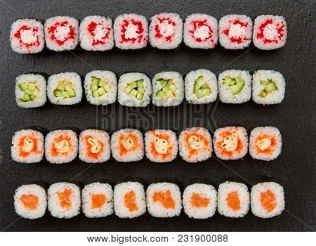 Big Set Of Sushi Roll On Slate. Japanese Food Restaurant. Dark Background. Top View.