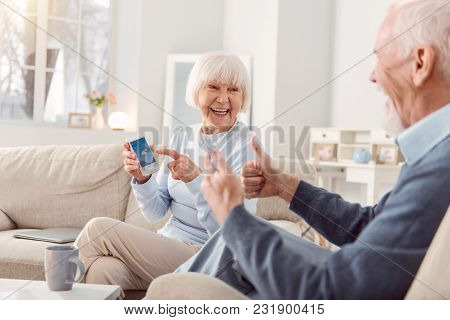 Great Weather. Cheerful Elderly Couple Sitting On The Couch In The Living Room, Checking The Weather
