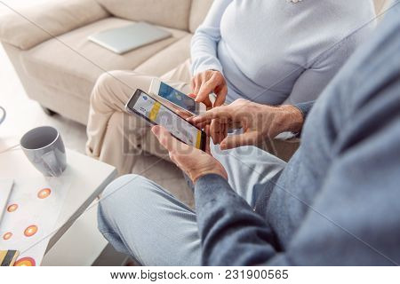 Helpful Technologies. The Close Up Of An Elderly Couple Sitting In The Living Room And Checking The