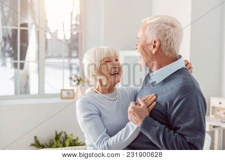 Loving Couple. Joyful Elderly Husband And Wife Dancing In The Living Room While Smiling At Each Othe