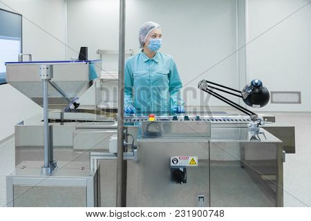 Pharmaceutical Technician In Sterile Environment Working On Production Of Pills At Pharmacy Factory