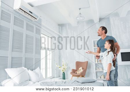 Climate Control. Joyful Positive Nice Girl Standing Together With Her Father And Holding A Remote Co