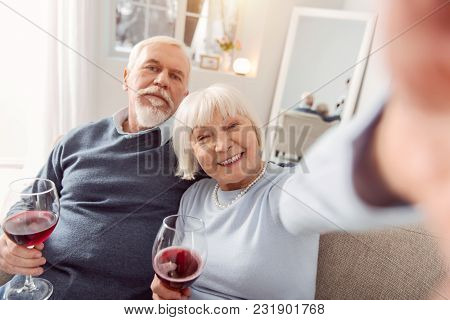 Seizing The Moment. Happy Elderly Couple Sitting On The Couch And Drinking Wine While Taking Selfies