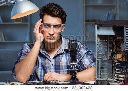 Repairman trying to repair laptop with miscroscope