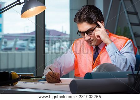 Construction architect working on drawings late at night