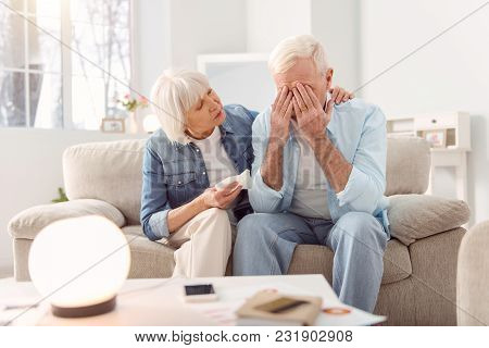 Stop Crying. Loving Elderly Woman Sitting On The Sofa Next To Her Crying Husband And Hugging Him, Tr