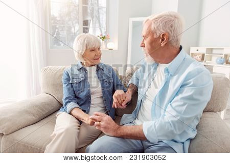 Loving Looks. Sweet Elderly Couple Sitting On The Couch And Holding Hands While Looking At Each Othe