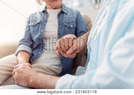 Together Till End. The Close Up Of Happy Elderly Couple Sitting On The Sofa And Holding Hands, The F