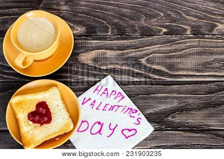 On A Wooden Background There Is A Cup Of Coffee With A Toast On Which A Jam In The Form Of A Heart.