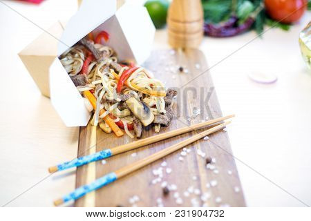 Wok. Noodles With Vegetables And Beef In Take-out Box On Wooden Table.