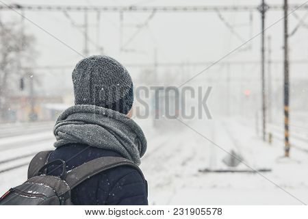 Railway In Winter. Young Man Traveling By Train During Heavy Snowfall