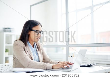 Secretary in eyeglasses typing on laptop at office