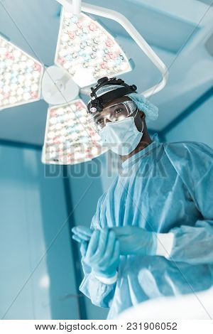 Bottom View Of African American Surgeon Wearing Medical Gloves And Looking Away