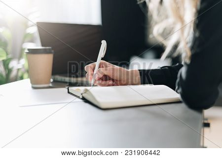 Close-up Of Notebook On Table And Pen In Female Hand. Girl Is Making A Note In A Notebook, Planning.