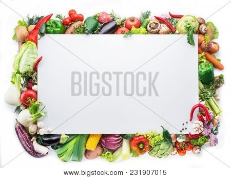 Different colorful vegetables arranged as a frame on white background. Free space for your text.