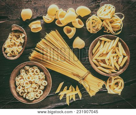 Different pasta types on the wooden table. Top view. Vintage style.