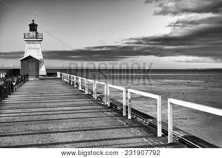 Old Fashioned Lighthouse On The End Of A Pier, Vast Water And Cloud Beyond. Black And White Art Imag