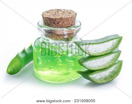 Aloe gel in the cosmetic jar and fresh aloe leaves on white background.