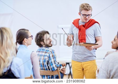 Young speaker with pencil and notepad explaining his ideas to one of students during lecture or seminar