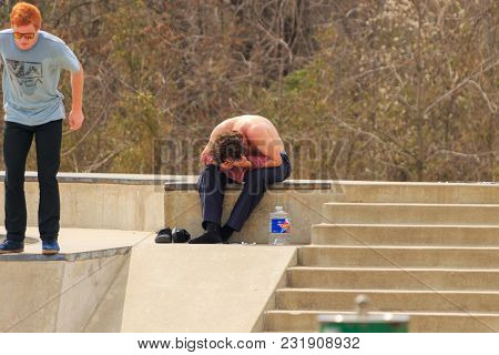 Tulsa, Oklahoma, March 2018, A Couple Unknown Young Men Are Wore Out From Skate Boarding At A Local