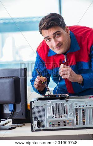 Computer technician repairing broken computer in workshop