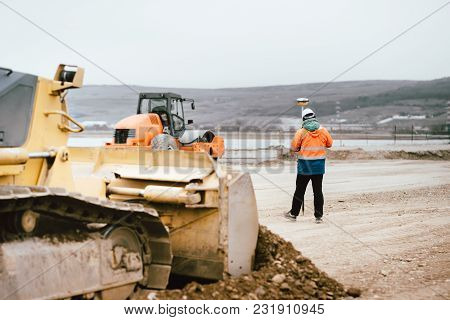 Surveyor Engineer With Gps System Outdoors At Highway Construction Site, Excavator And Bulldozer Det