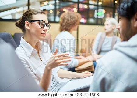 Pensive young woman explaining her point of view to one of co-workers during discussion of new design trends