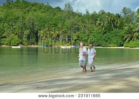 Happy Elderly Couple Running  On Sandy Beach