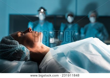 Side View Of Surgeons Looking At Female Patient In Operating Room