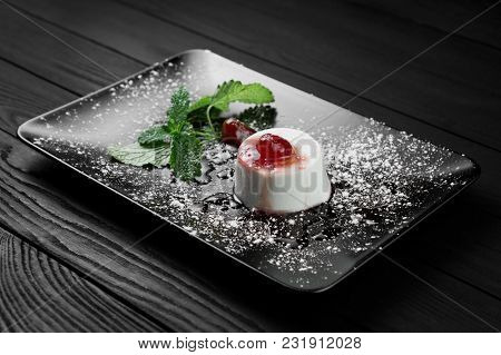 Photo Of Italian Panna Cotta Dessert With Strawberry Sirup And Mint Leaf On The Black Wooden Backgro