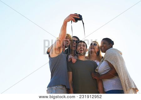 Ecstatic young friendly people making selfie on photocamera against sunshine
