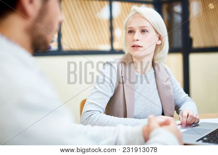 Pretty blonde manager looking at colleague while discussing data for business project