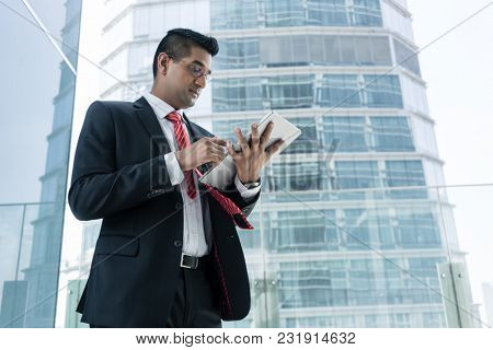 Indian businessman analyzing financial report on a tablet PC indoors at the office