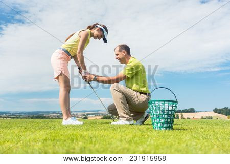 Full length side view of a young woman holding an iron club, while exercising the golf swing helped by her experienced instructor outdoors on green grass
