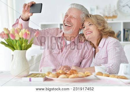 Happy Senior Couple With Smartphone Drinking Tea At Kitchen