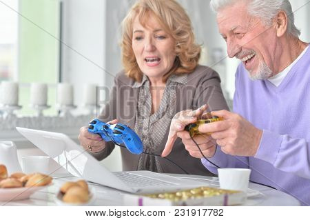 Happy Senior Couple Playing Computer Game With Laptop While Drinking Tea At Kitchen