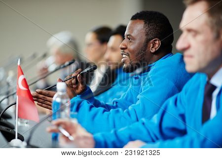 Young professional sportsman speaking in microphone during press conference