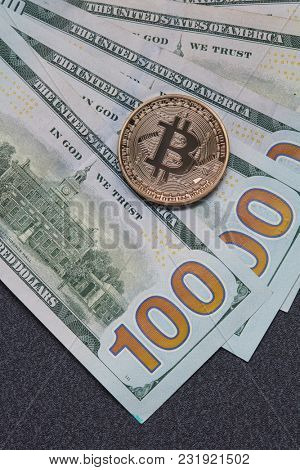 Gold coin bitcoin and new hundred dollar bills. Exchange of Crypto-Currency for Dollars