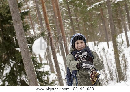 A Smiling, Happy Woman Throws A Snowball Playfully In The Winter Forest.