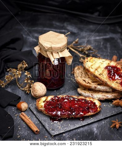 Toast Of White Bread With Raspberry Jam And A Glass Jar With Jam On A Black Background, Top View
