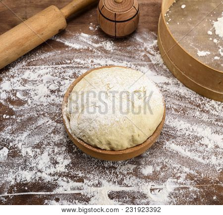 Yeast Dough From White Wheat Flour In A Wooden Bowl On A Table With Flour