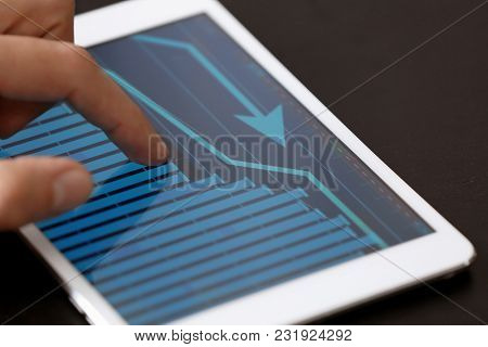 Man using tablet computer with stock chart data on screen, closeup. Forex concept