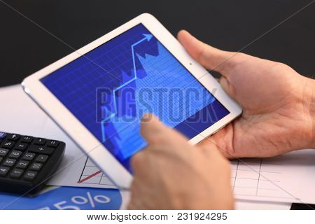 Man using tablet computer with stock chart data on screen at table. Forex concept