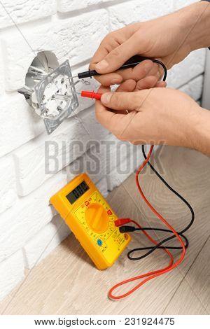 Electrician measuring voltage of socket