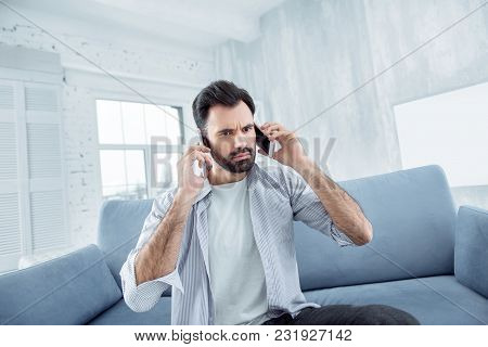 Listening To You. Concentrated Man Pressing Lips And Wrinkling Forehead While Talking Per Telephone